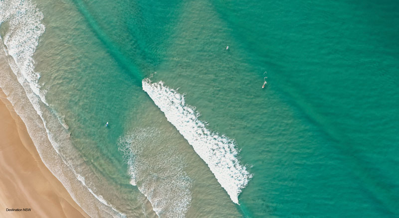 Drone view of aqua waves crashing on to sand