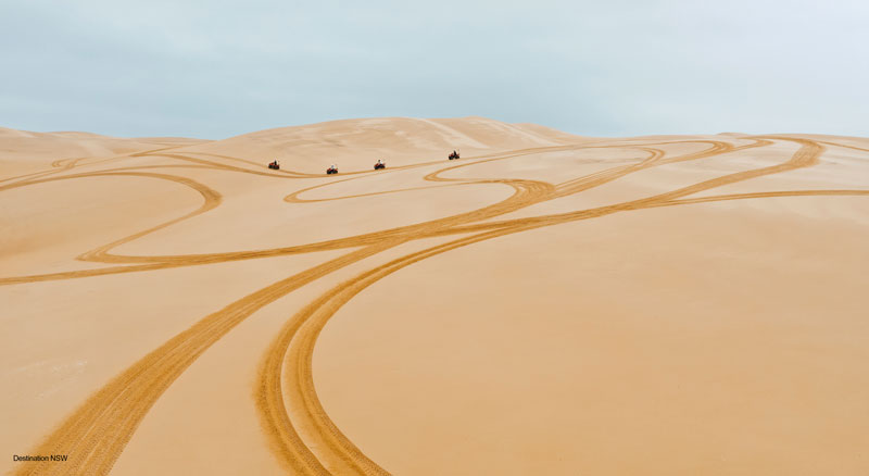 Quad bikes drawing lines on the sand dunes